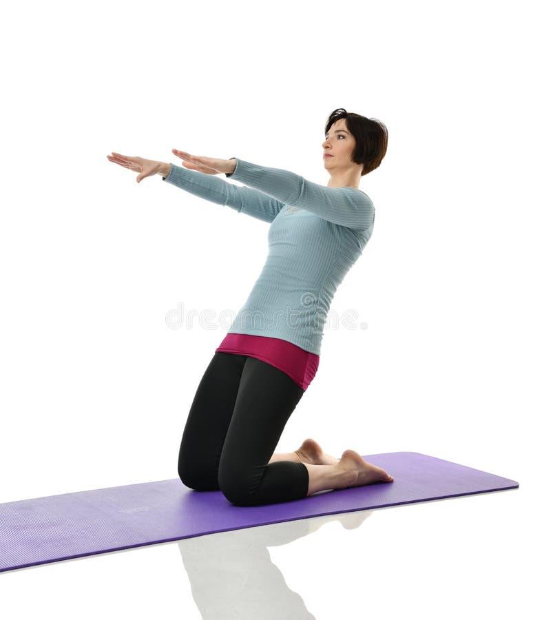 Żeński sprawność fizyczna instruktor robi rozciąganiu dla ręk nóg abdominals baru ćwiczenia w gym opracowywał odosobnionego na bi obraz royalty free