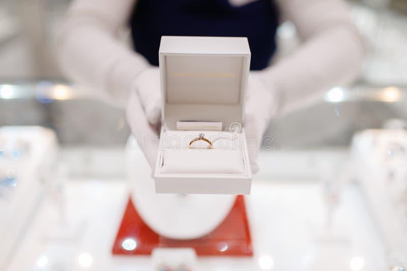 Żeński sprzedawca wręcza chwytom złocistego diamentowego pierścionek w pudełku zdjęcia stock