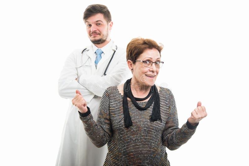 Żeński starszy cierpliwy robi zwycięzcy gest z samiec lekarką zdjęcie stock