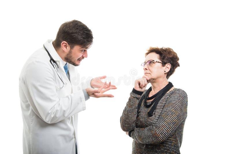 Żeński starszy pacjent wyjaśnia coś samiec lekarka zdjęcia stock