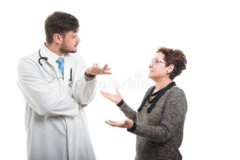 Żeński starszy pacjent wyjaśnia coś samiec lekarka zdjęcie royalty free