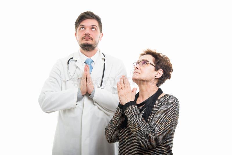 Żeński starszy pacjenta i samiec doktorski ono modli się wpólnie zdjęcie royalty free
