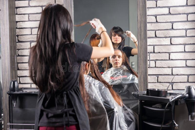 Żeński stylista gruntownie farbuje włosy młoda kobieta z paintb zdjęcie stock