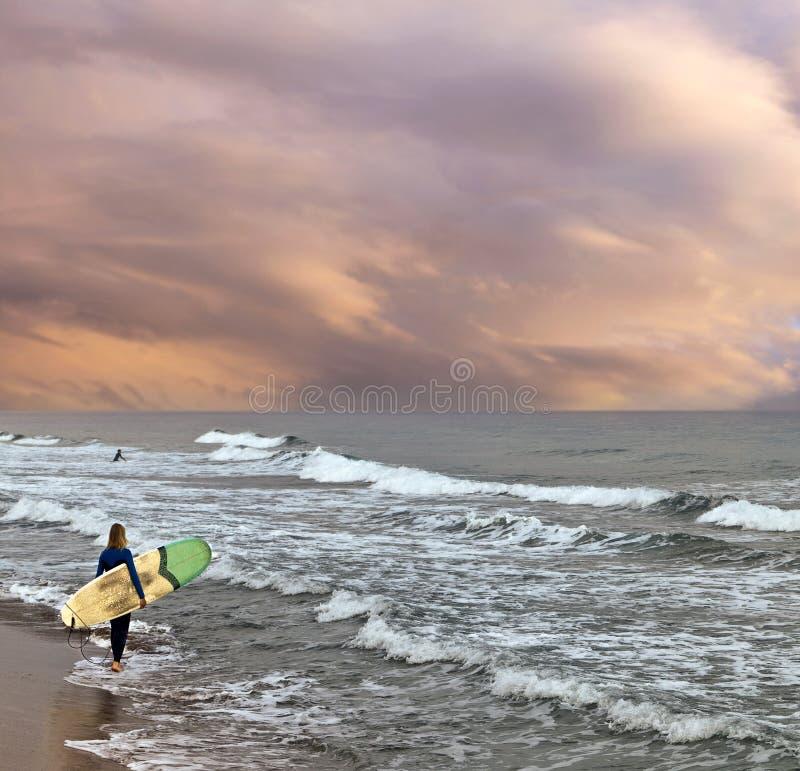 Żeński surfingowiec na plaży przy zmierzchem z burzowym morzem i surfboard fotografia stock