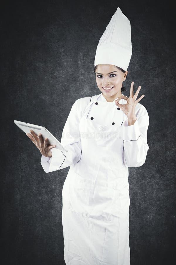 Żeński szef kuchni pokazuje OK podpisuje wewnątrz studio fotografia stock