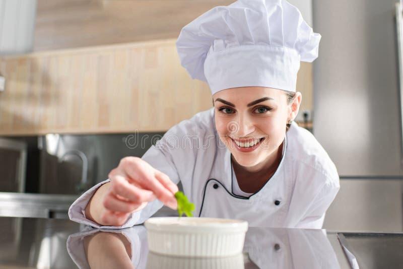 Żeński szefa kuchni garnirowania naczynie zdjęcia stock
