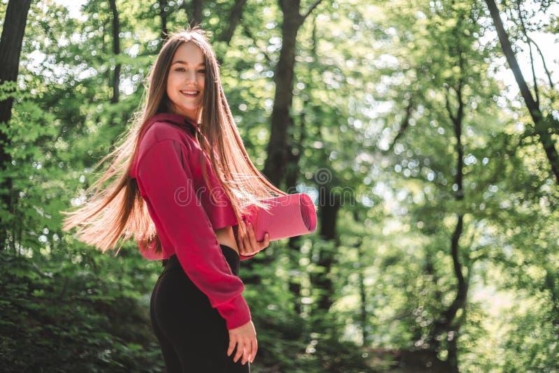 Żeński trzepotliwy włosy w hoodie z sprawności fizycznej matą na trenować plenerowy zdjęcia royalty free