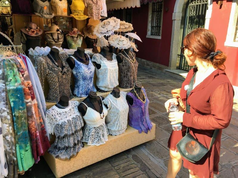 Żeński turystyczny zakupy dla koronkowej odzieży przy sklepem w Burano, Włochy zdjęcie stock