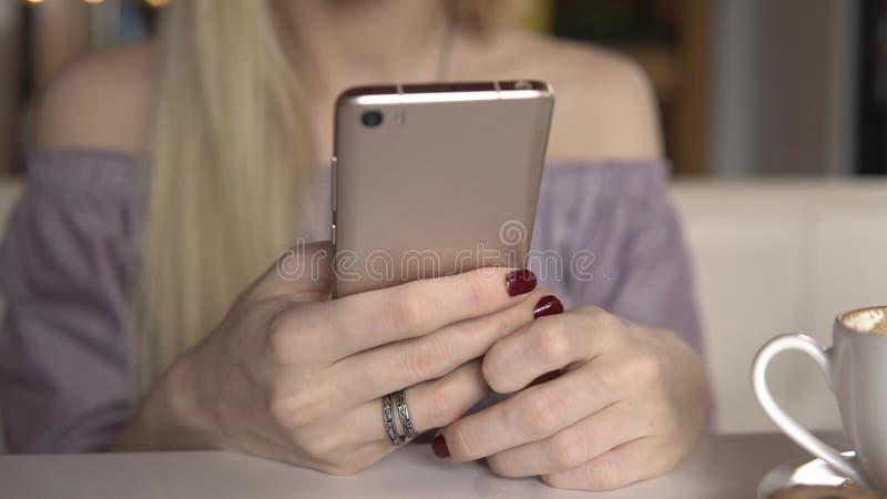 Żeński używa smartphone podczas gdy pijący kawę zdjęcia royalty free