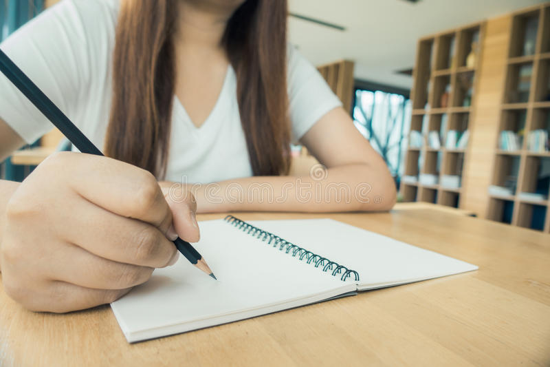 Żeński uczeń bierze notatki od książki przy biblioteką Młody azjatykci kobiety obsiadanie przy stołem robi przydziałom w szkoły w zdjęcia royalty free