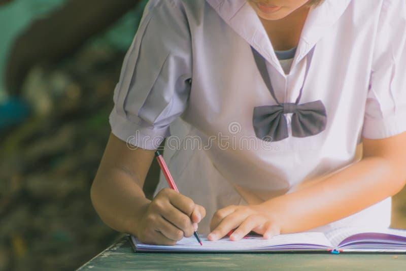 Żeński uczeń pisze notatniku dla absolwentów w drugorzędnym schoo fotografia stock
