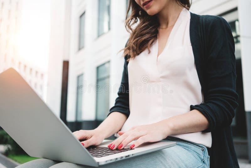 Żeński uczeń przygotowywa dla coursework z nowożytnym laptopem na miastowej ulicie przed uniwersytetem fotografia royalty free