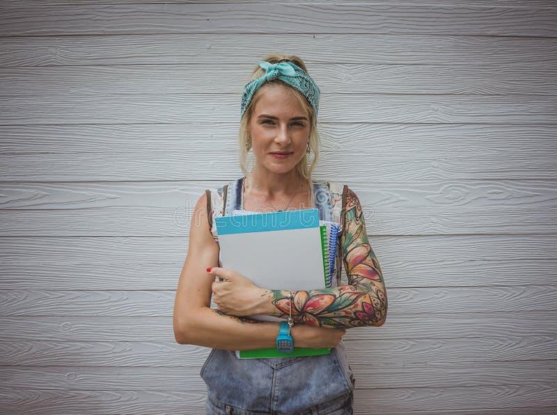 Żeński uczeń stoi białą ścianą z notatnikami w jego rękach w oczekiwaniu na klasy nowoczesna dziewczyna model zdjęcia royalty free