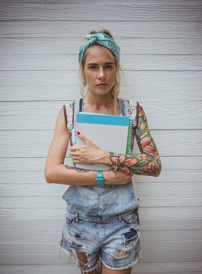 Żeński uczeń stoi białą ścianą z notatnikami w jego rękach w oczekiwaniu na klasy nowoczesna dziewczyna model zdjęcia stock