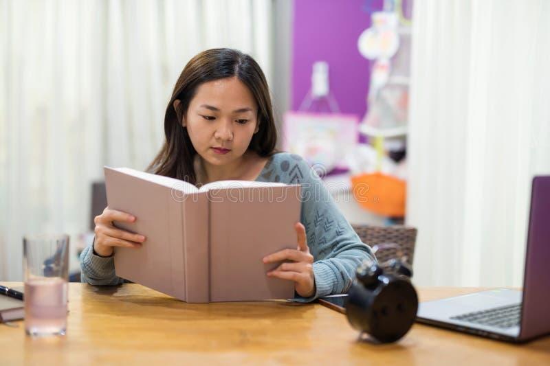 Żeński uczeń w domu czyta tekst książkę zdjęcia royalty free