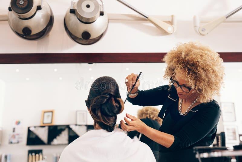 Żeński włosiany stylista pracuje na kobiety ` s włosy przy salonem zdjęcia royalty free
