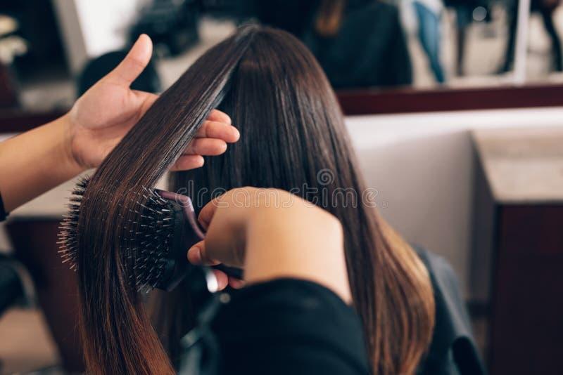 Żeński włosiany stylista pracuje na kobiety ` s włosy przy salonem zdjęcia stock