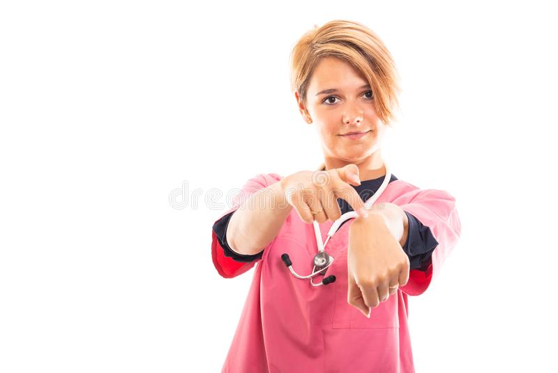 Żeński weterynarz jest ubranym menchie szoruje pokazywać wskazujący wristwatch gestu zdjęcie stock
