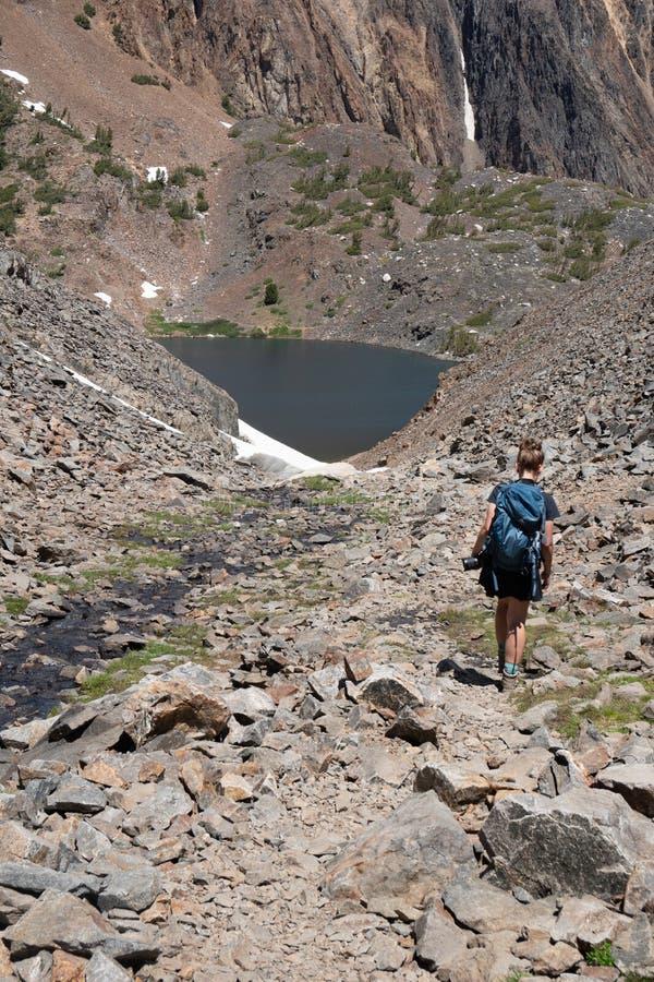 Żeński wycieczkowicz chodzi wzdłuż śladu skalisty piarg i talus wzdłuż 20 jezior Basenowego terenu Kalifornia góry fotografia stock