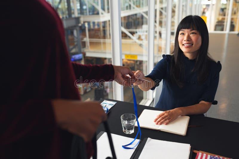 Żeński wykonawczy daje pracownika id bizneswoman przy konferencyjnym rejestracja stołem obraz royalty free