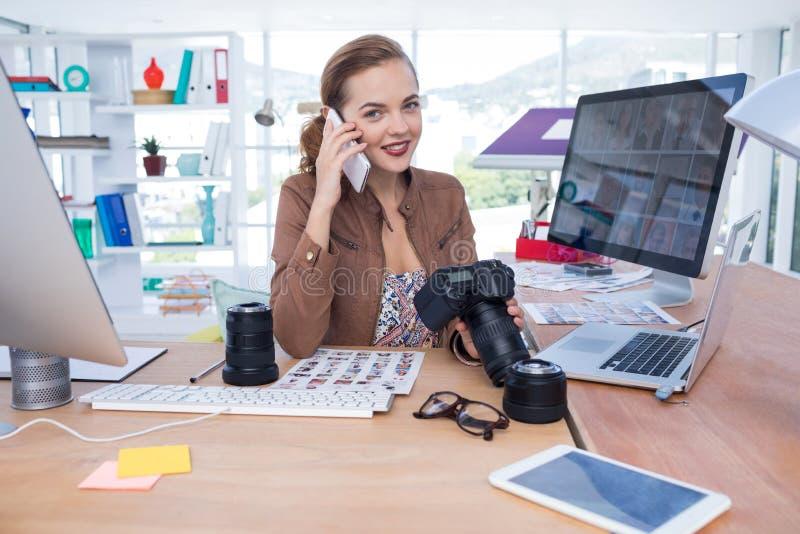Żeński wykonawczy opowiadać na telefonie komórkowym w biurze zdjęcie stock