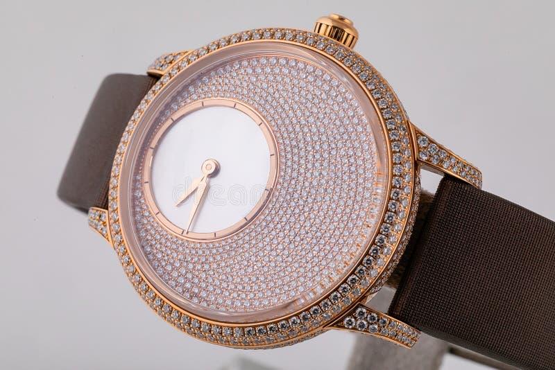 Żeński złocisty wristwatch z tarczą od kamieni, złoty clockwise, na brąz sukiennej patce na białym tle zdjęcie stock