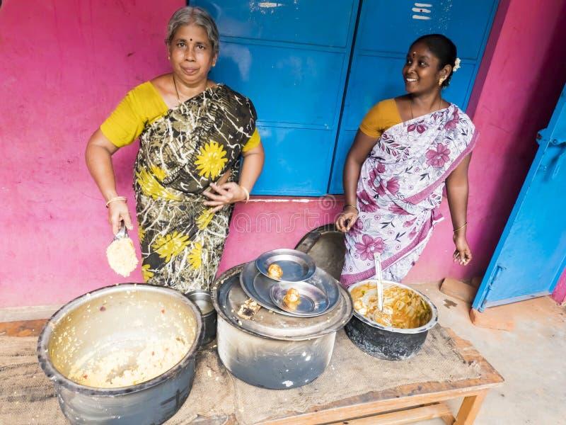 Żeńskich kobiet workerwith stołówkowy sari outdoors z kucharstwo garnkiem z ryż i masala obraz stock