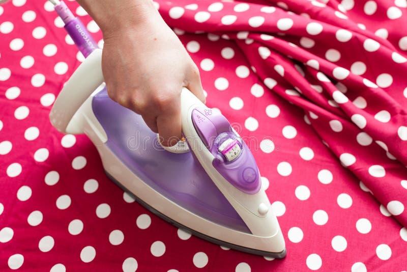 Żeńskich ręki prasowania ubrań odgórny widok podczas sprzątania Zakończenie gosposi ręki prasowanie odziewa na prasowanie desce w fotografia royalty free