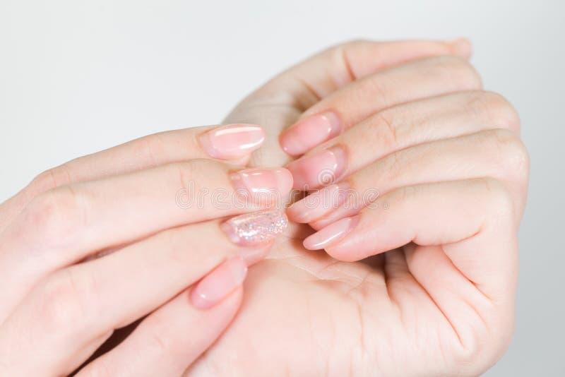 Żeńskie białe ręki z stary gel polerującym manicure'em potrzebują korekcję fotografia stock