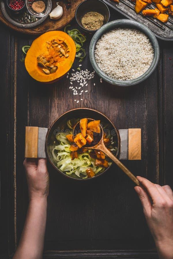 Żeńskie kobiet ręki trzyma garnek, łyżka i kulinarny dyniowy risotto na ciemnym nieociosanym kuchennym stole z składnikami, odgór zdjęcia stock