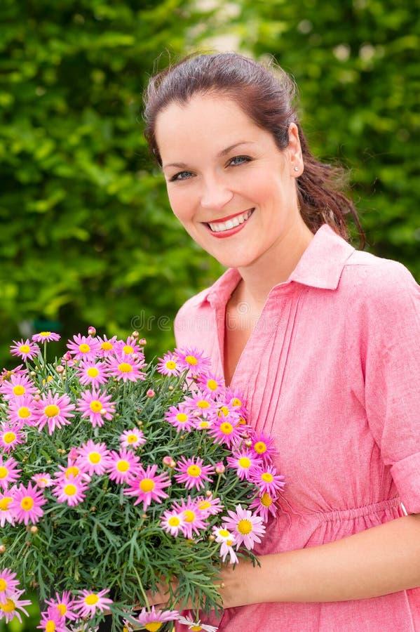 Żeńskie kwiaciarni chwyta menchie puszkujący kwiat obraz stock