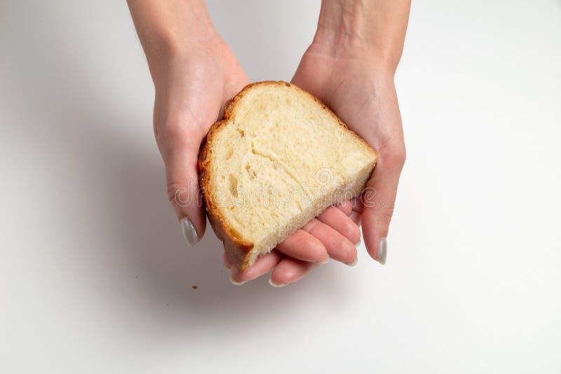 Żeńskie ręki dają białemu chlebowi na tle, stole białych/ Mi?dzynarodowy dzie? Pomaga? bied? obrazy royalty free