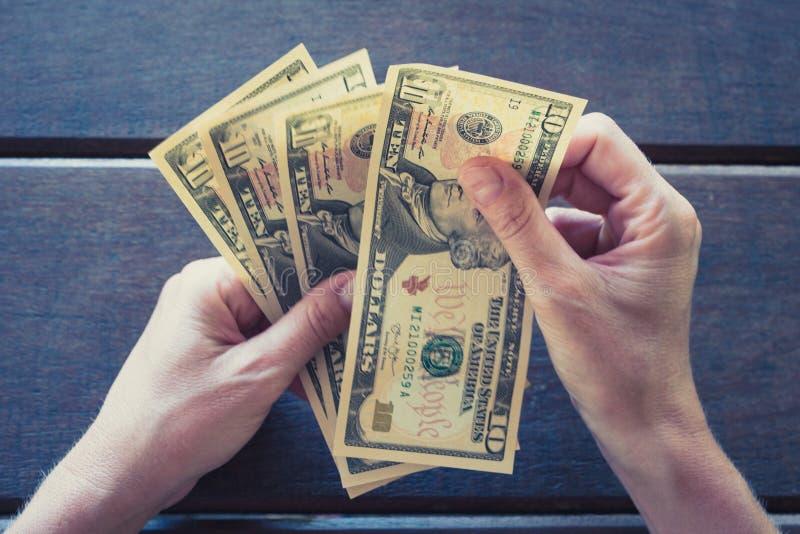Żeńskie ręki liczy dziesięć dolarowych rachunków - gotówkowy pieniądze USD obraz royalty free