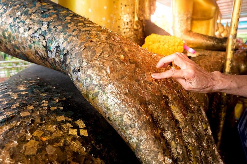 Żeńskie ręki są ozłacającym Buddha statuą zdjęcia stock