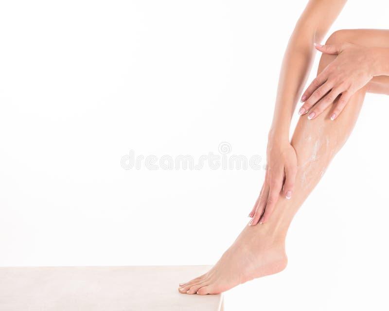 Żeńskie ręki stosuje ciało śmietankę na jej nodze, zakończenie w górę zdjęcie stock