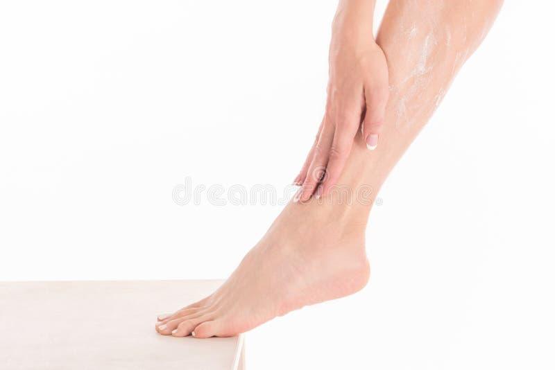 Żeńskie ręki stosuje ciało śmietankę na kobiety nodze, zakończenie w górę zdjęcie stock