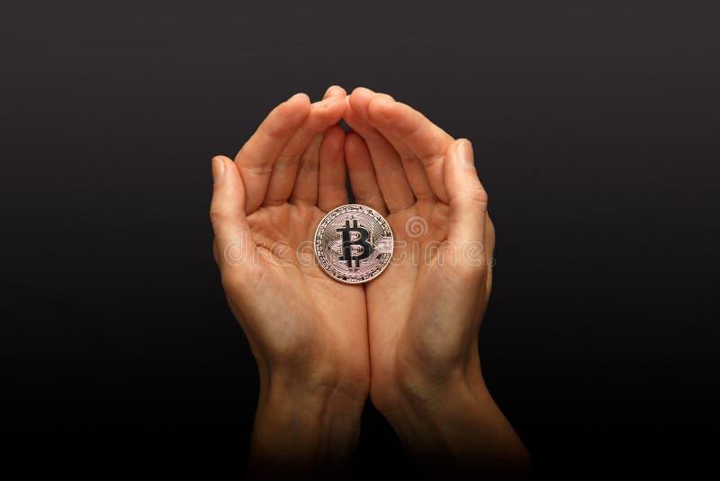 Żeńskie ręki trzyma srebnego Bitcoin zdjęcie stock