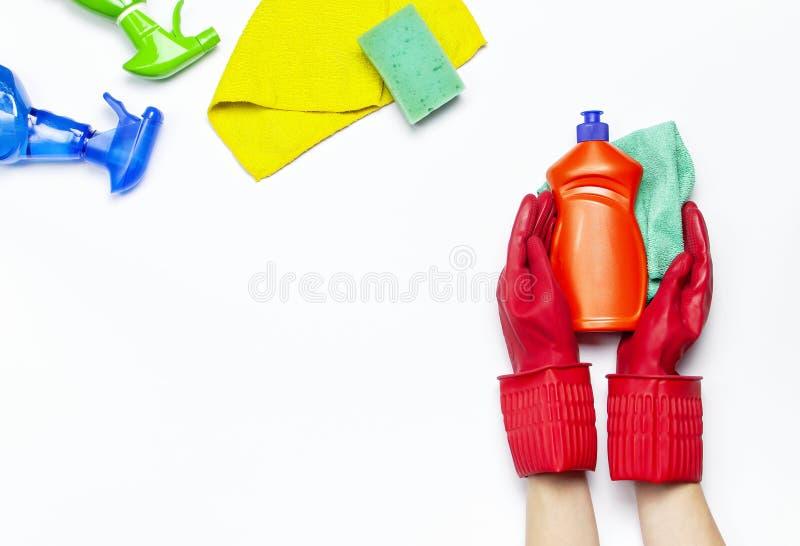 Żeńskie ręki w czerwonych gumowych ochronnych rękawiczkach z microfiber płótnem odizolowywającym na białej tło odgórnego widoku k fotografia stock