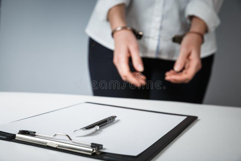 Żeńskie ręki w kajdankach wypełniają za policja raportu rozpoznaniu obrazy royalty free