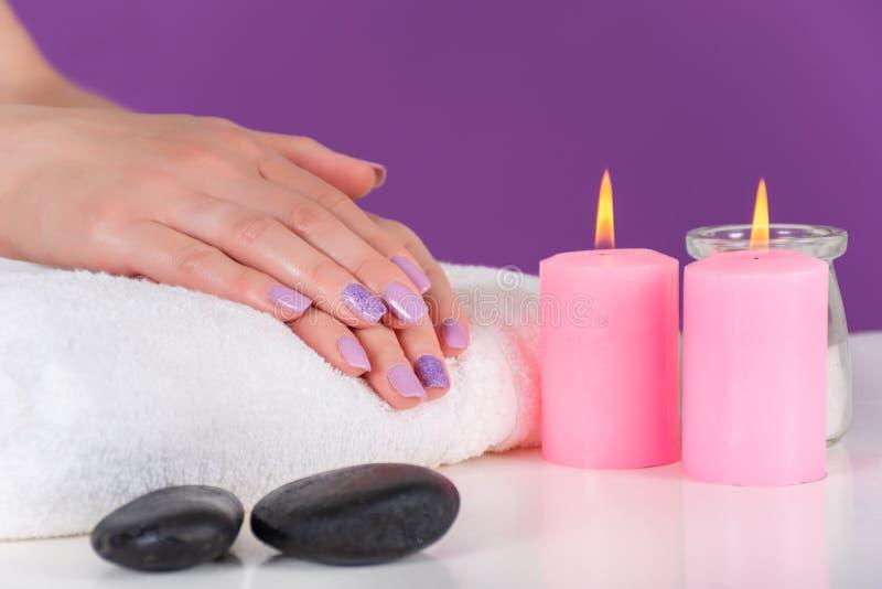 Żeńskie ręki z lilym kolorem robią manikiur na białym ręcznika, menchii dekoracji świeczki paleniu na i purpury tle i biurku fotografia royalty free
