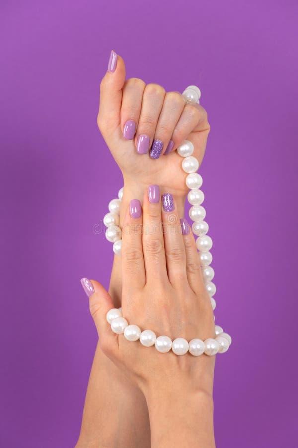 Żeńskie ręki z lilym koloru manicure'u mieniem operlają kolię odizolowywającą na purpurowym tle obraz royalty free