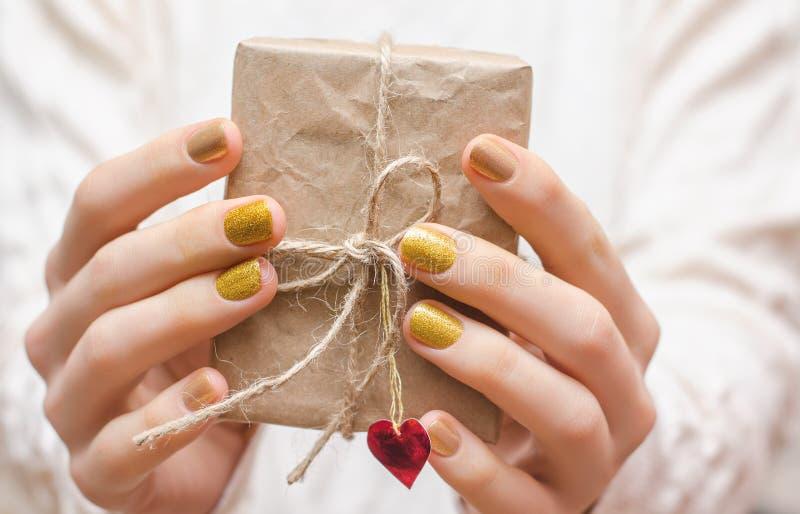 Żeńskie ręki z złocistym gwoździa projektem zdjęcie stock