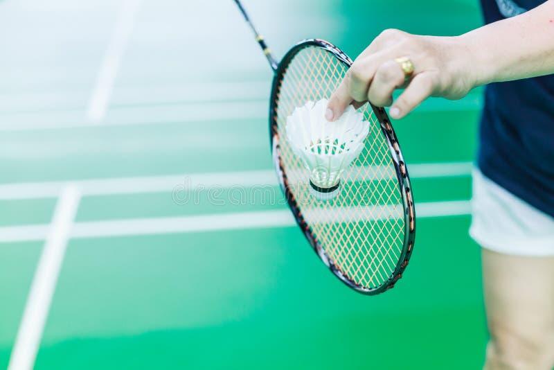 Żeńskiego Badminton pojedynczego gracza ręki chwyta wahadłowa biały kogut z kantem, gotowym słuzyć backhand pozycję na sztuki zie fotografia royalty free