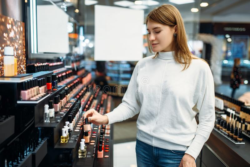 Żeńskiego klienta przyglądający kosmetyki w makeup sklepie obraz royalty free