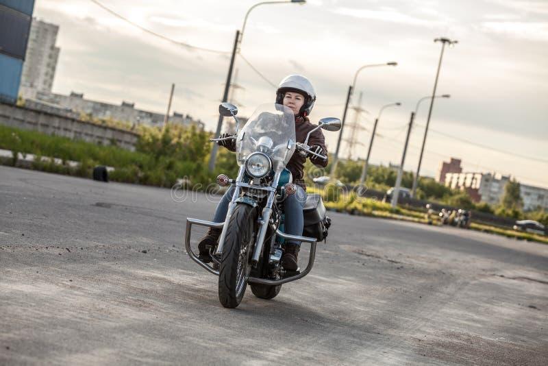 Żeńskiego motocyklisty napędowy solo na asfaltowej drodze na motocyklu zdjęcia royalty free
