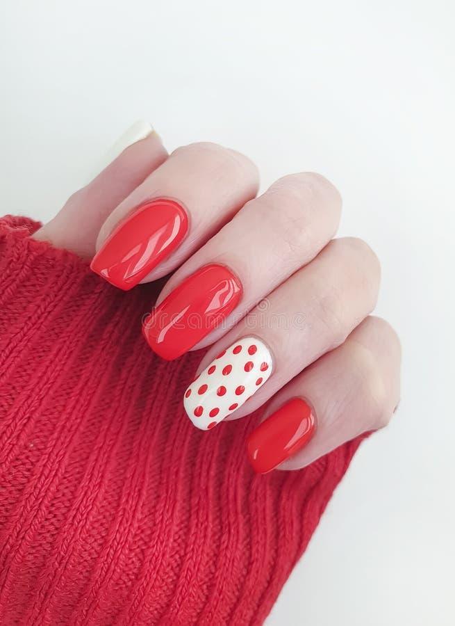 Żeńskiego ręka pięknego projekta manicure'u dekoracji czerwony pulower elegancki obraz royalty free