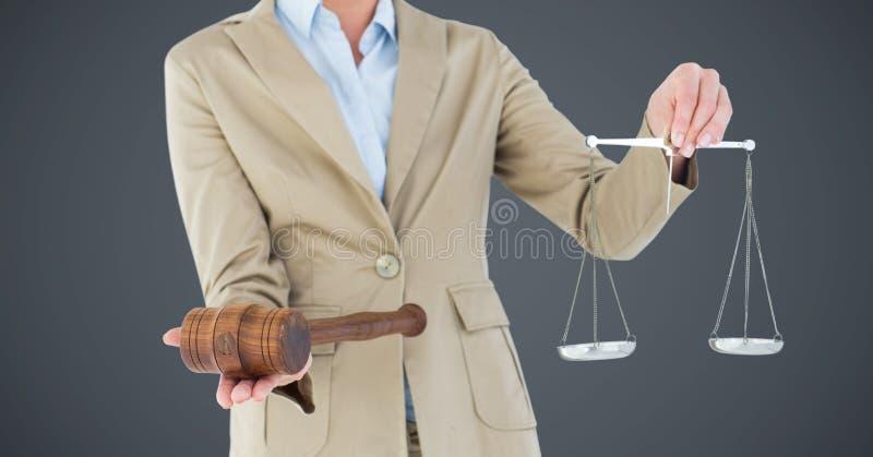 Żeńskiego sędziego w połowie sekcja z waży przeciw popielatemu tłu i młoteczek fotografia royalty free