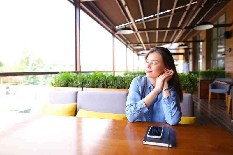 Żeńskiego ucznia obsiadanie przy kawiarnią z smartphone i notatnikiem na stole zdjęcia stock