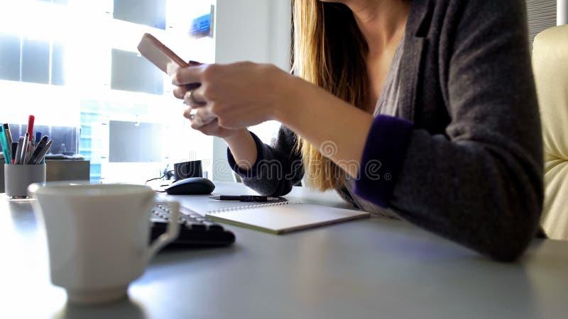 Żeńskiego urzędnika wiadomości czytelniczy smartphone, mianuje spotkania z klientem zdjęcie royalty free