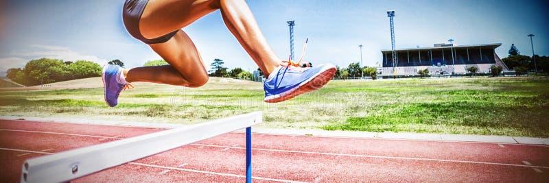 Żeńskiej atlety doskakiwanie nad przeszkoda obrazy royalty free